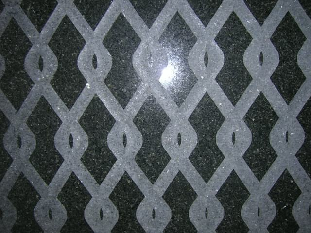 Percoco's Chain-link pattern of concave smooth tooled interlocking waves shown on a piece of San Gabriel granite