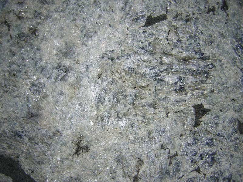 Percoco's Flamed and Brushed finish shown on a piece of Multicolor Labradorite granite