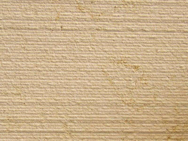 Percoco's Scarpaletto (Fine) finish shown on a piece of Halila Gold Limestone