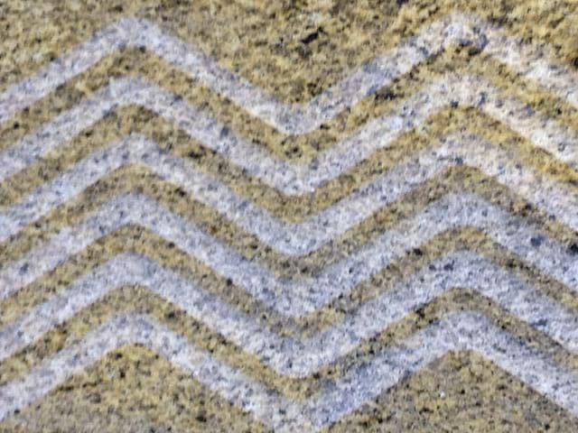 Percoco's Wave pattern of alternating flat polished and concave smooth tooled surface shown on a piece of Juperana Santa Ceceila granite